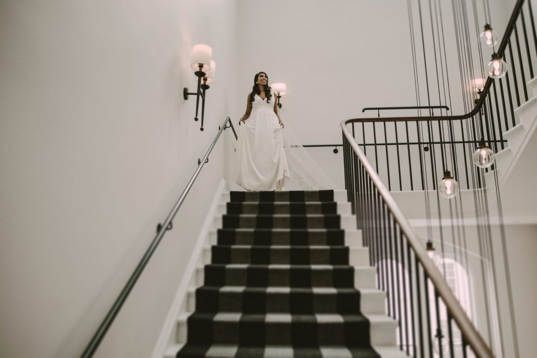 Yasime walking down the stairs in her wedding dress at the gainsborough hotel in Bath