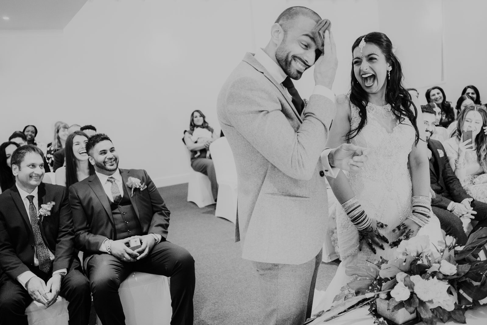 Rav and Vy laughing at their ceremony at priston mill in bath