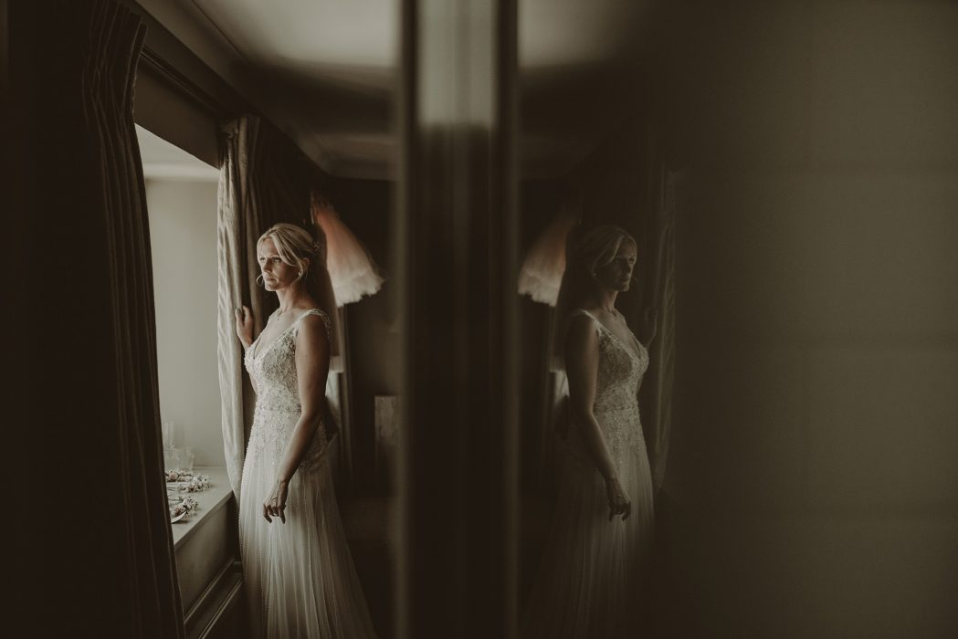 Bride looking out of the window at cripps barn in the cotswolds
