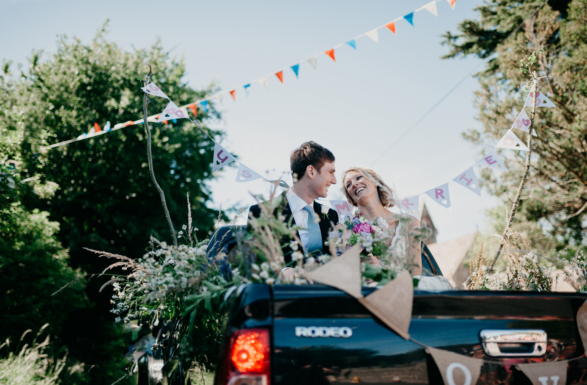 Bride and groom leaving church in a pick up truck