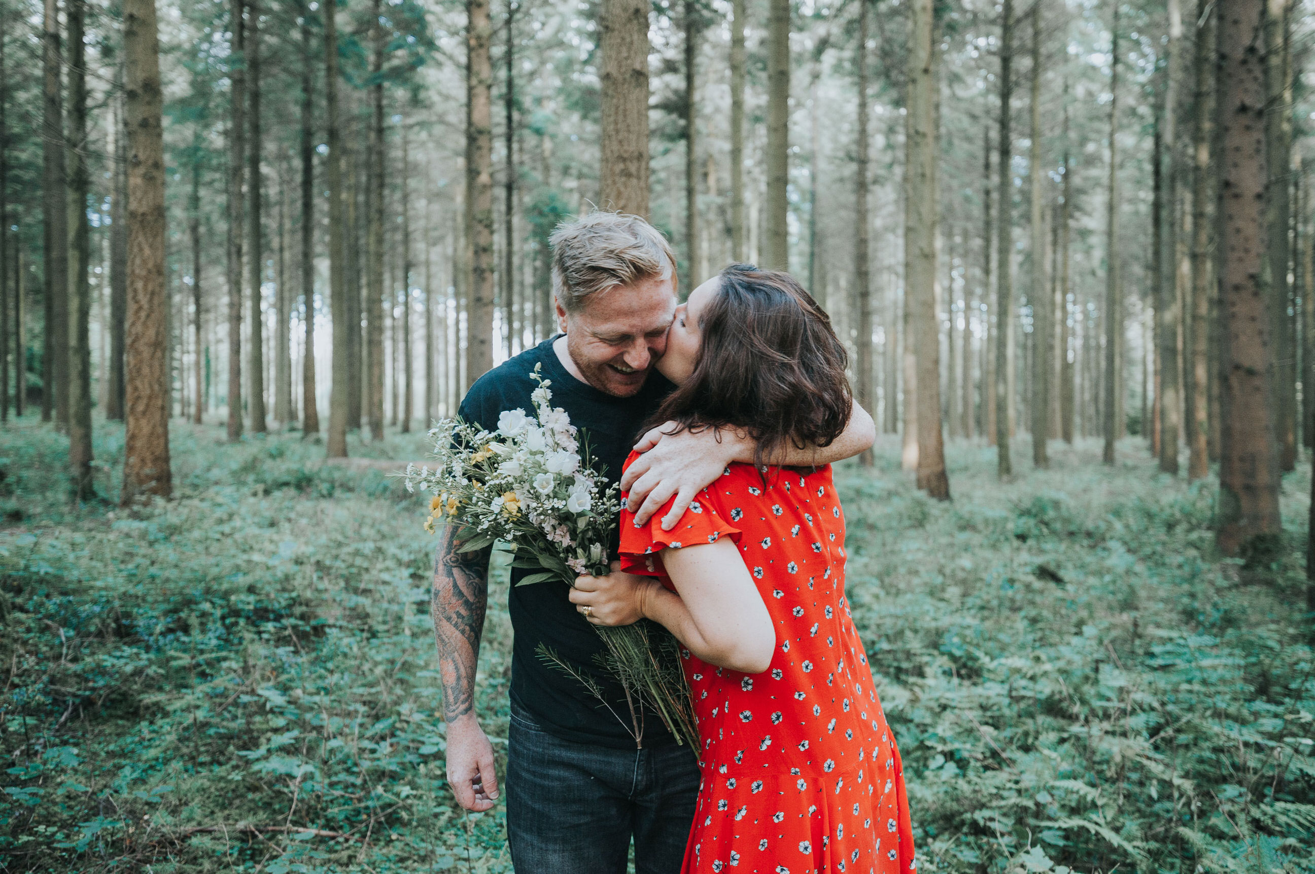 Husband and wife share a cuddle in the woods