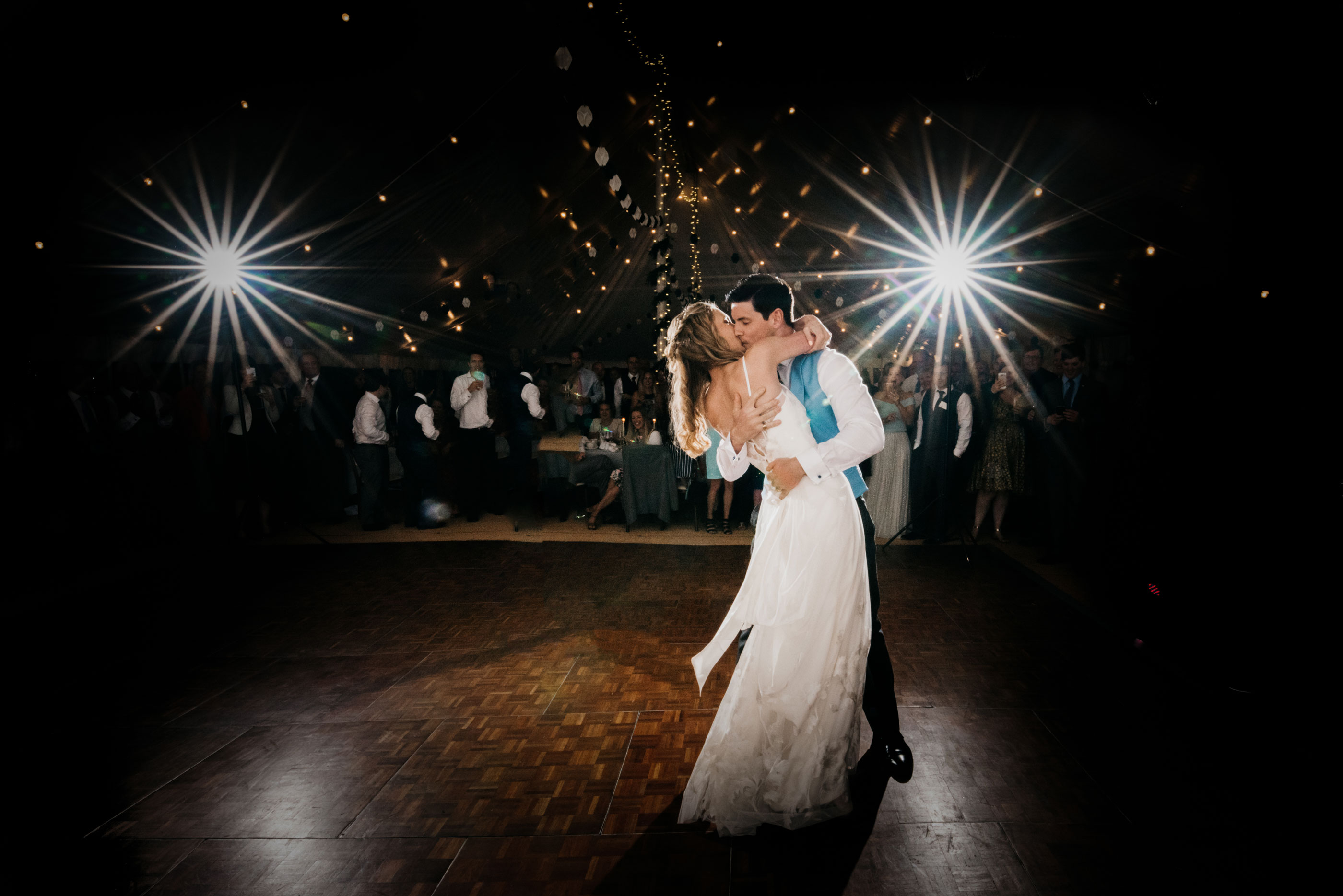 bride and groom sharing their first dance with flash lights in the background