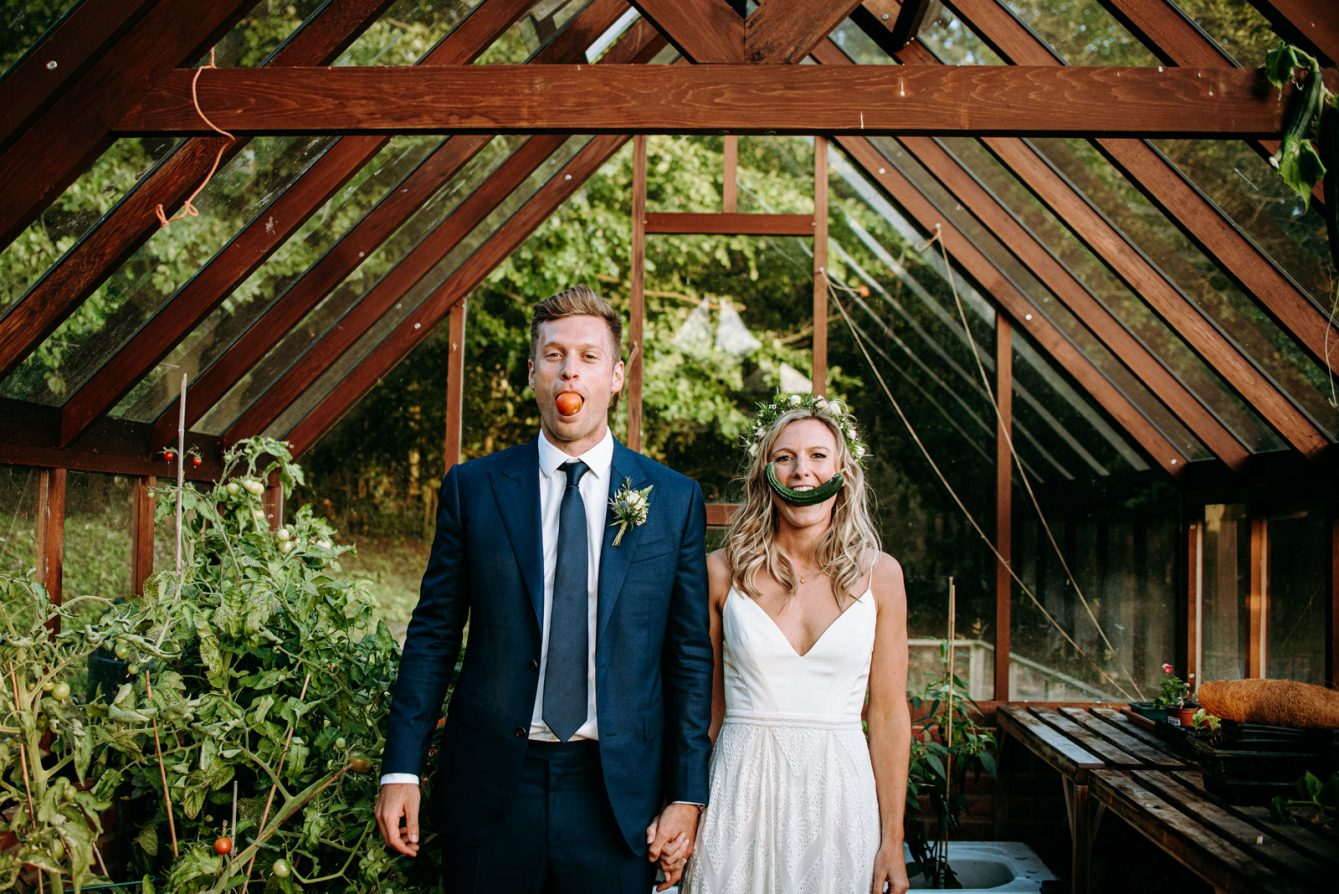 Mark and katie in the greenhouse with vegetables in thiner mouth on their wedding day