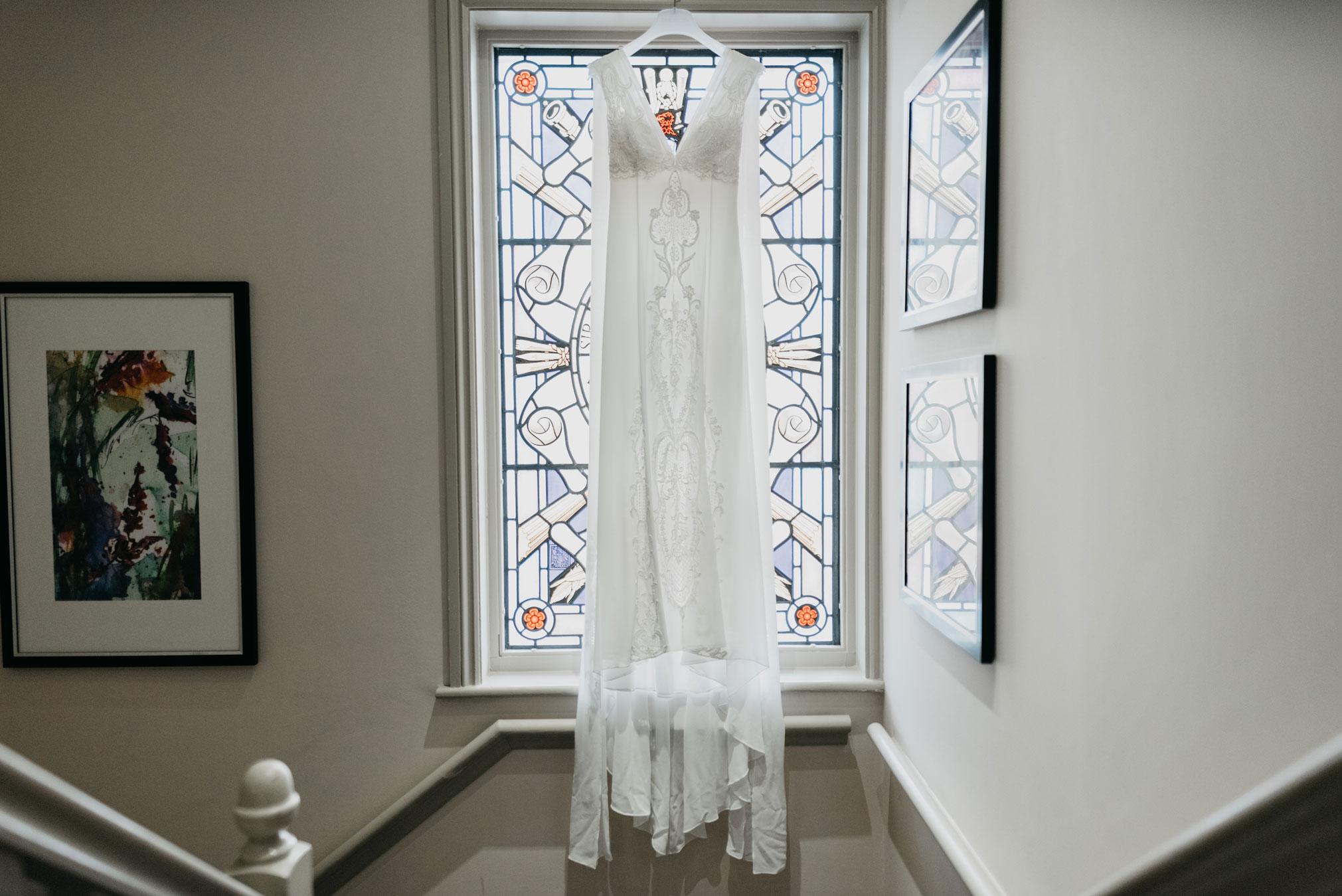brides dress hung up at the window