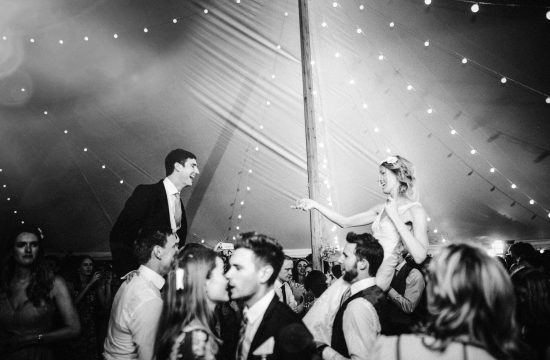 bride and groom on people's shoulders dancing and singing at night in marquee