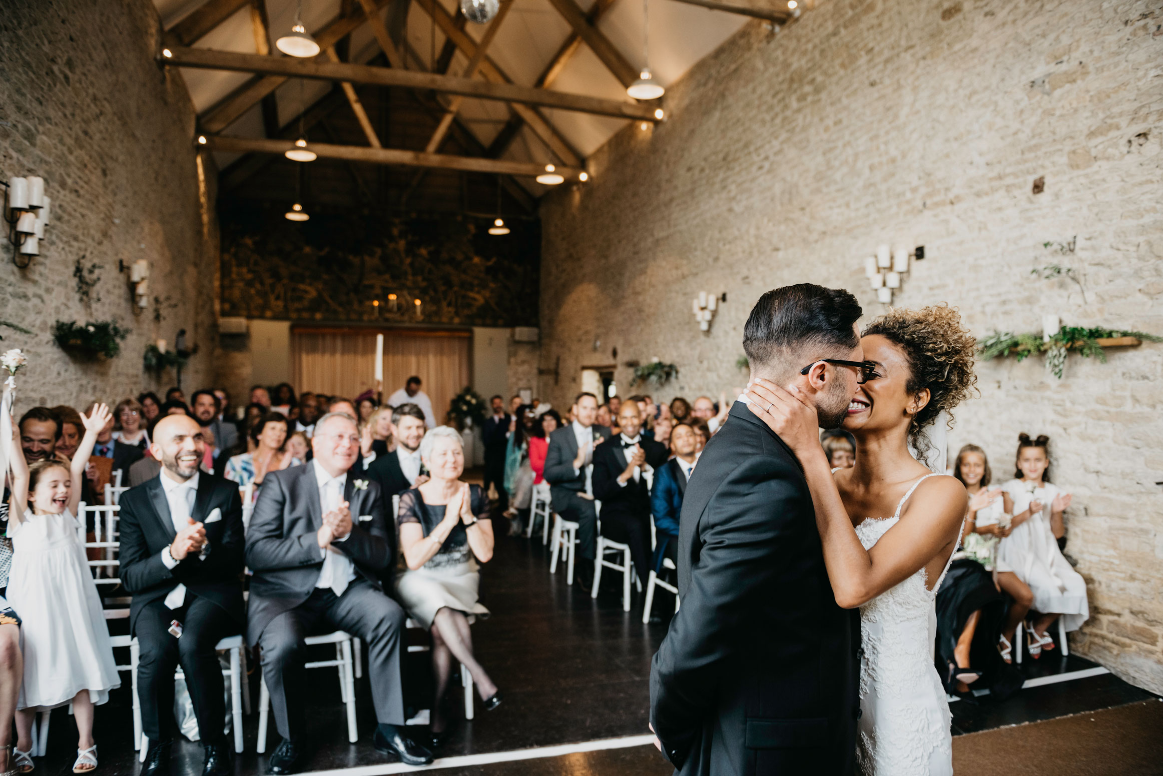 bride and grooms first kiss at merriscourt barn in chipping Norton
