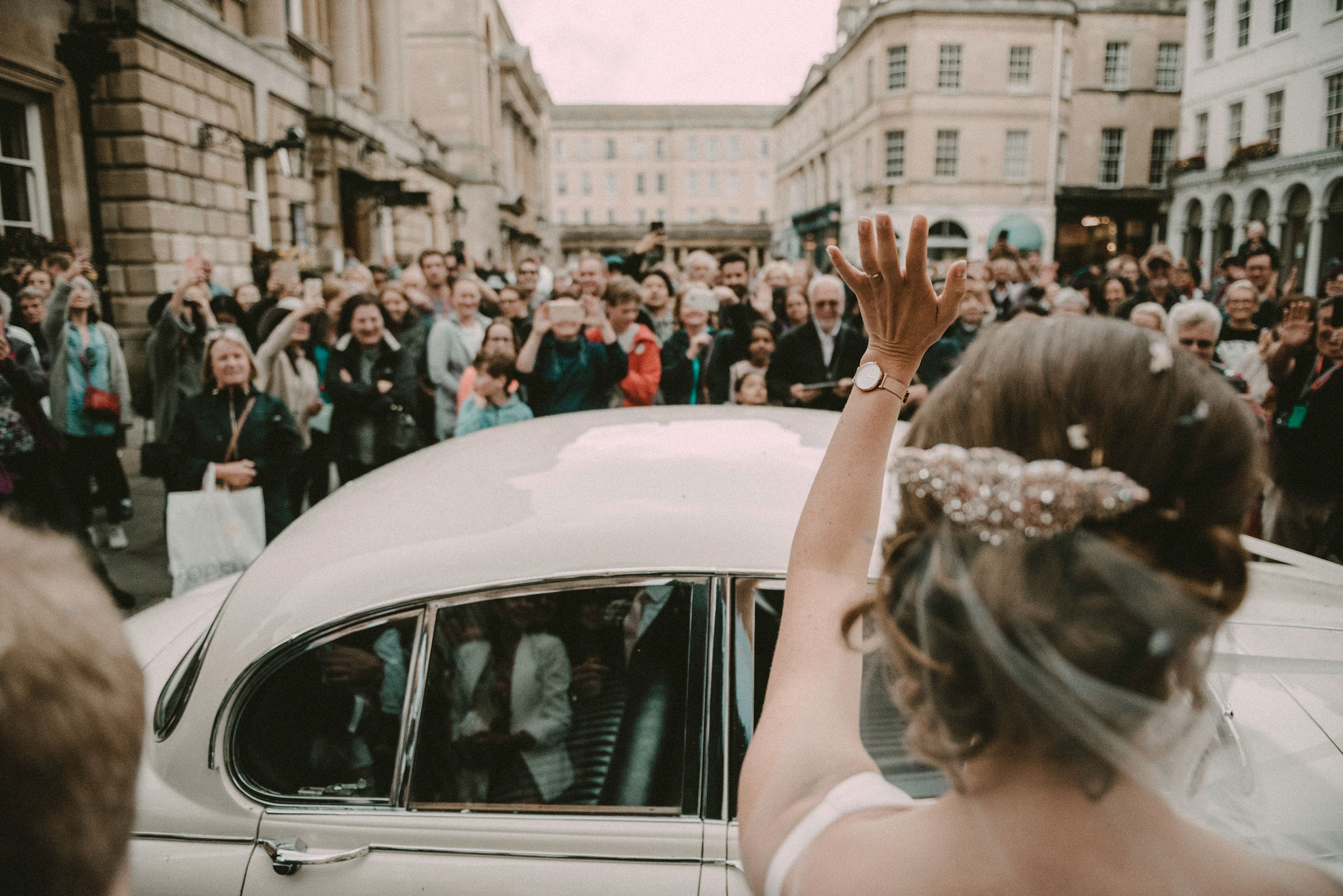 bride waves to the crowds outside Bath Abbey