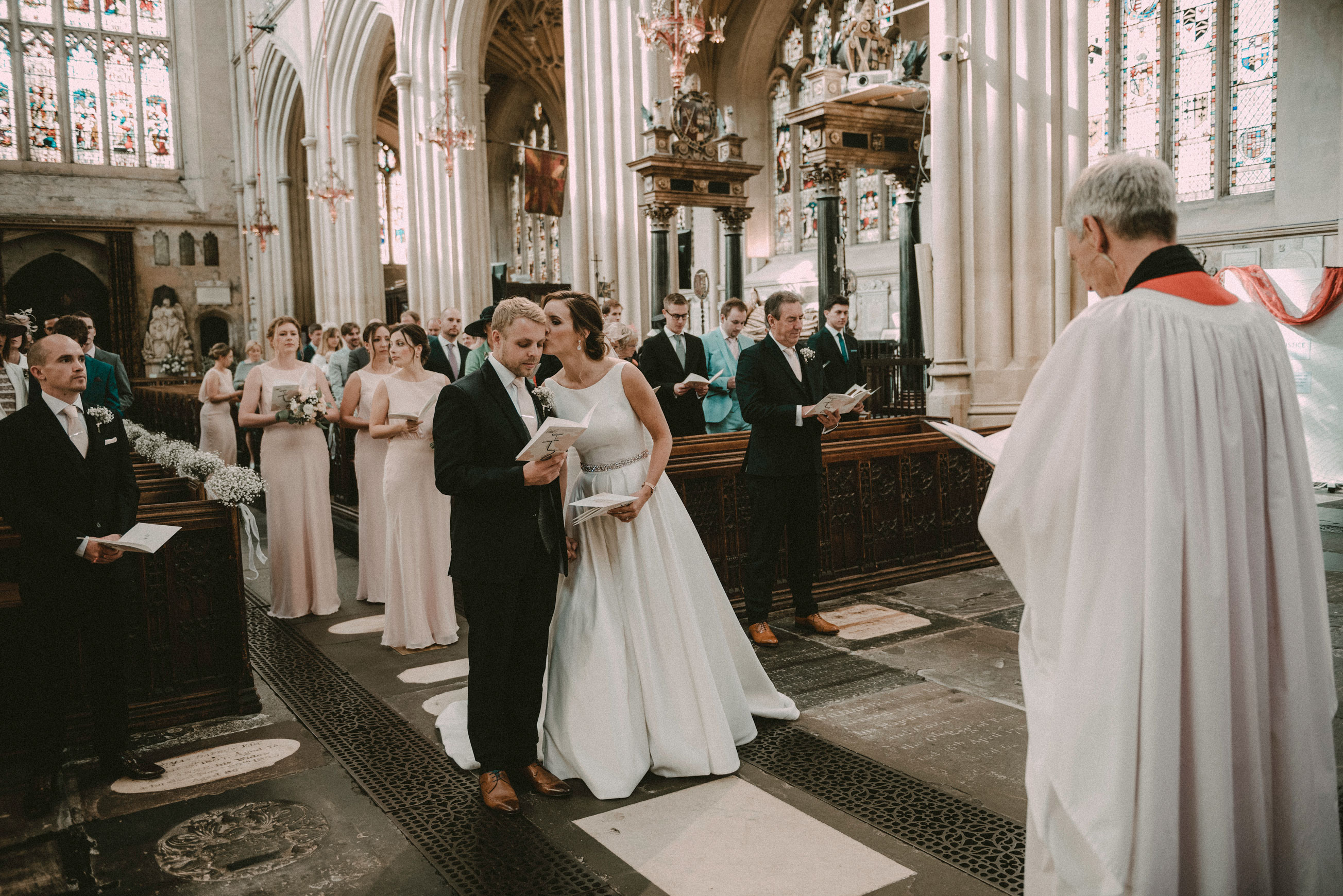 Bride gives groom a kiss in Bath Abbey