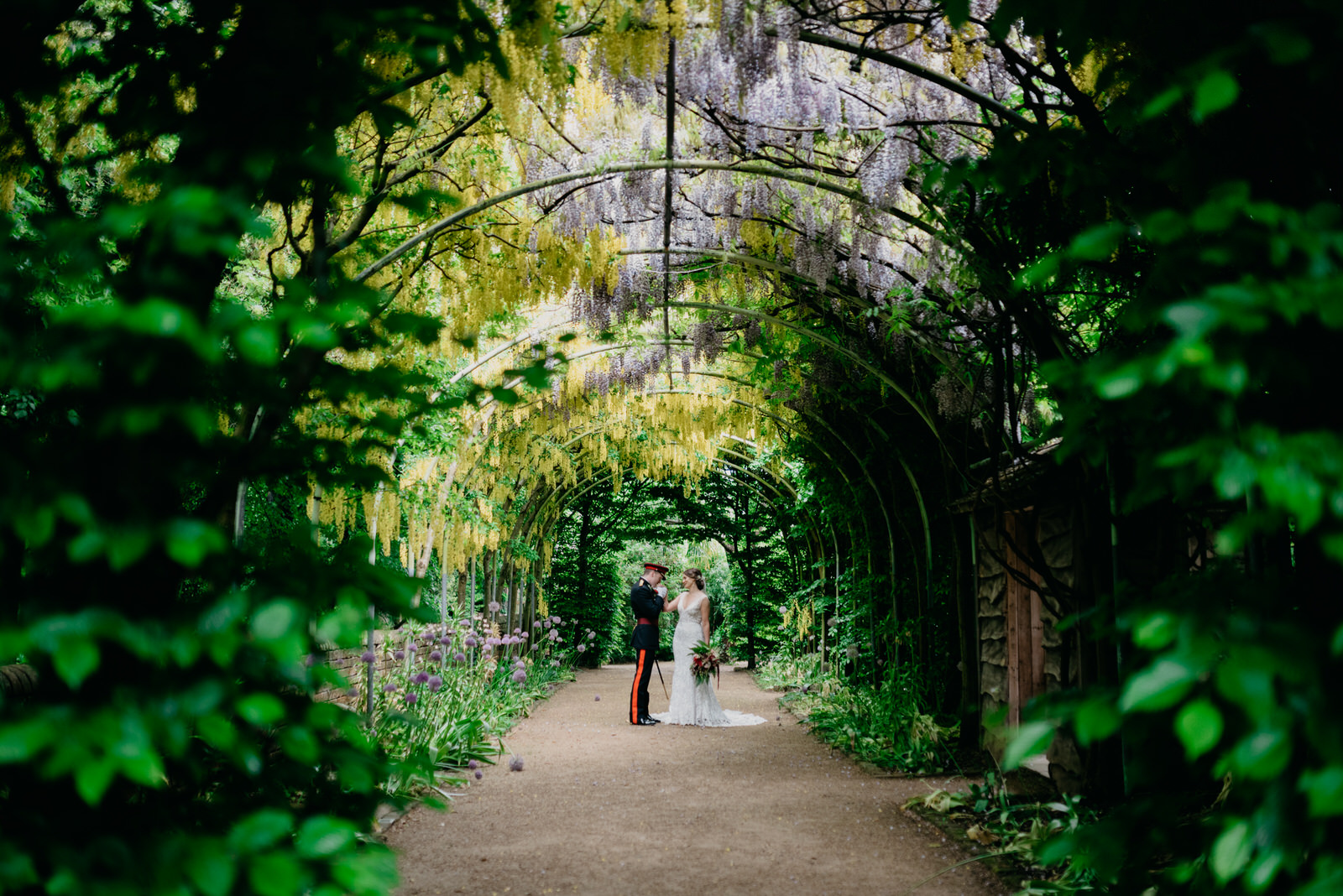 bride and groom in military uniform kissing under wisteria arch
