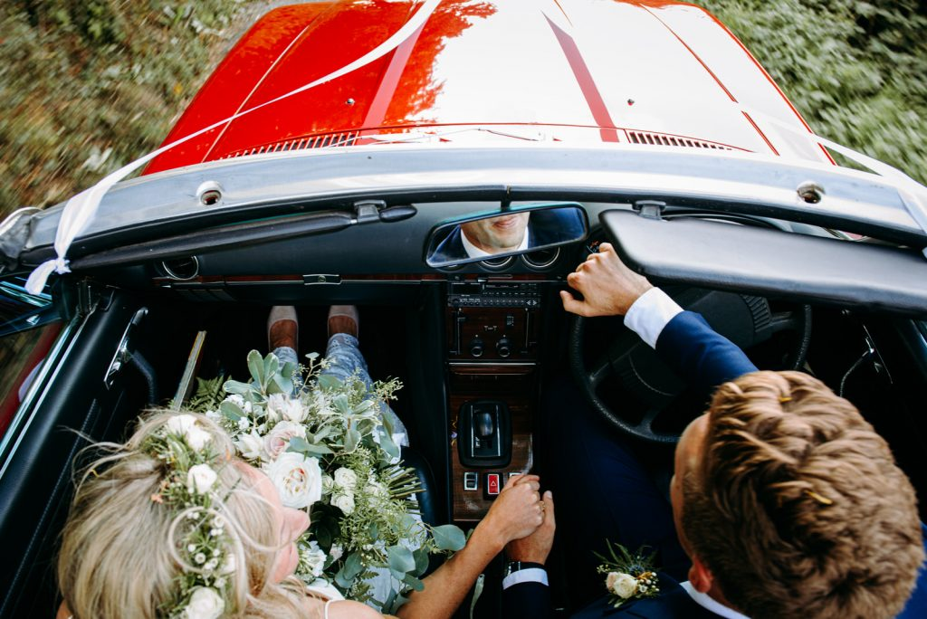 mark and katie driving in their wedding car