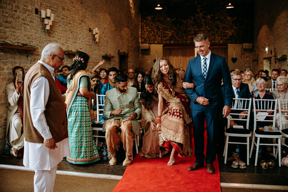 the bride and her uncle walking down the aslie in the indian ceremony at Merriscourt Barn in the Cotswolds
