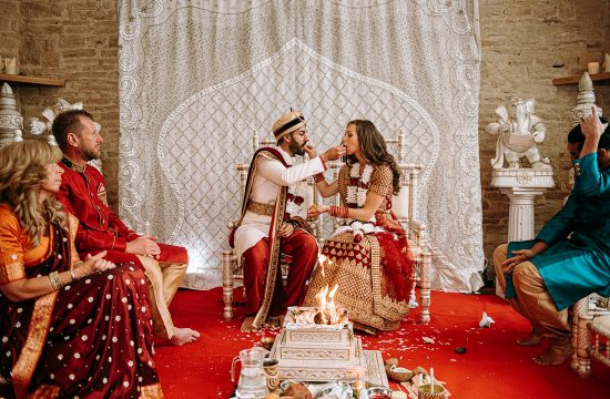 Bride and groom at Indian wedding ceremony feeding each other