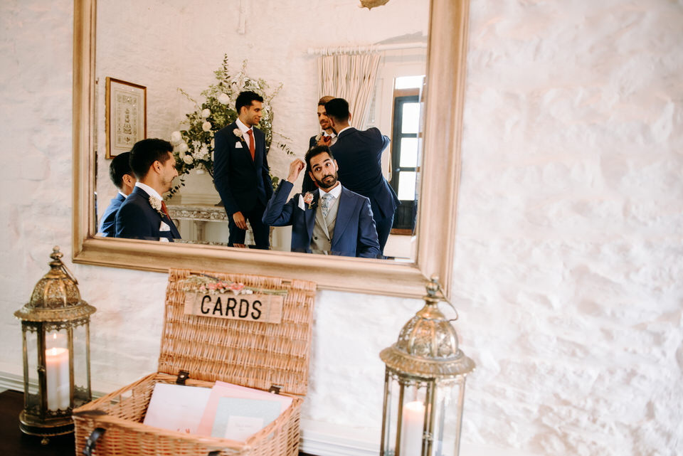 the groom checkinh his hair out in the mirror before the ceremony at Merrsicourt barn